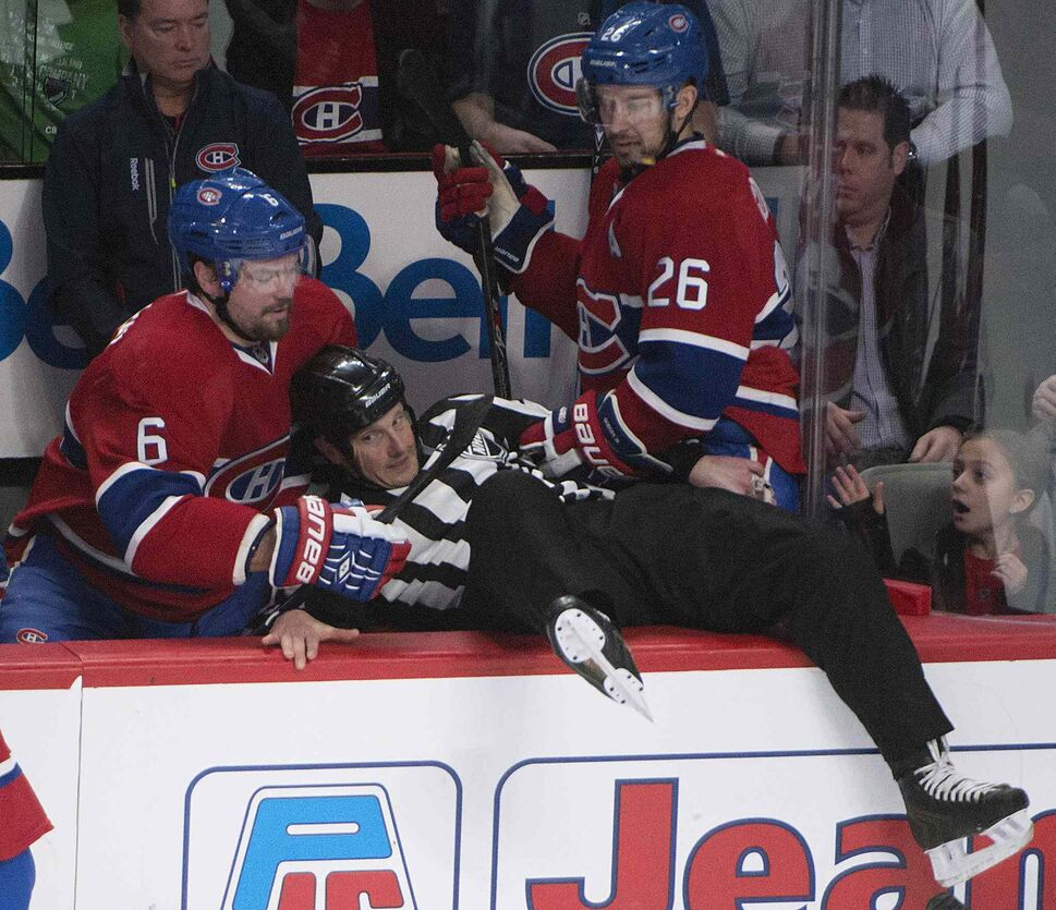 Linesman Darren Gibbs ended up in the Montreal bench during action Sunday in Montreal. (Peter McCabe / The Canadian Press)