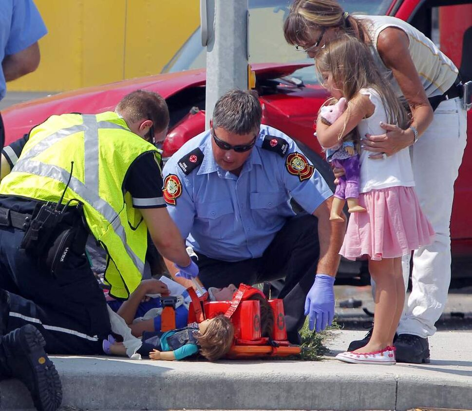 Two young girls are comforted and treated after an accident on McGillivray Boulevard.  July 13, 2012  (BORIS MINKEVICH / WINNIPEG FREE PRESS)