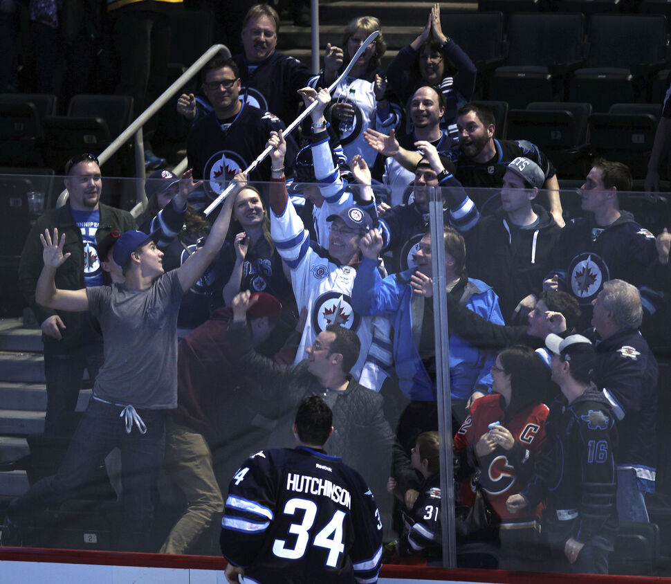 Fans scramble for Winnipeg Jets netminder Maichael Hutchinson's game stick at the MTS Center after he was awarded the first star of the game after a 2-1 shootout victory over the Boston Bruins. April 10, 2014 (Phil Hossack / Winnipeg Free Press)