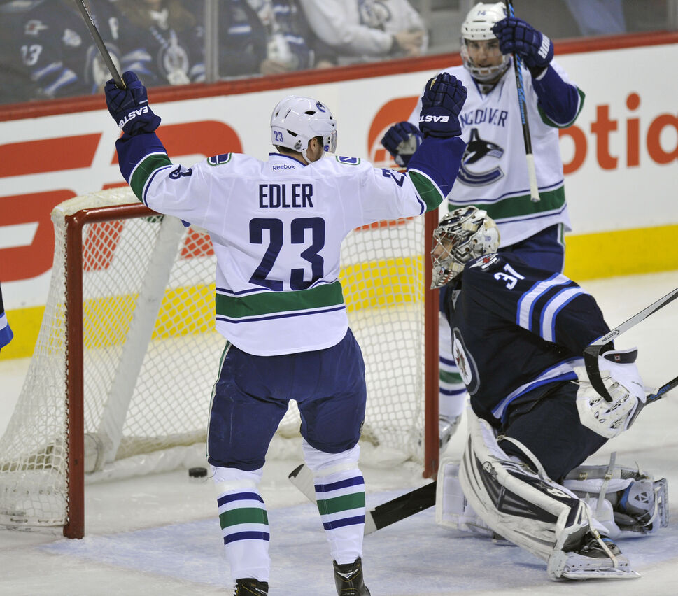 Winnipeg Jets' goaltender Ondrej Pavelec looks at the puck in the net as Vancouver Canucks' Alexander Edler celebrates his first-period goal in Winnipeg Friday. (Fred Greenslade  / Special for the WINNIPEG FREE PRESS)