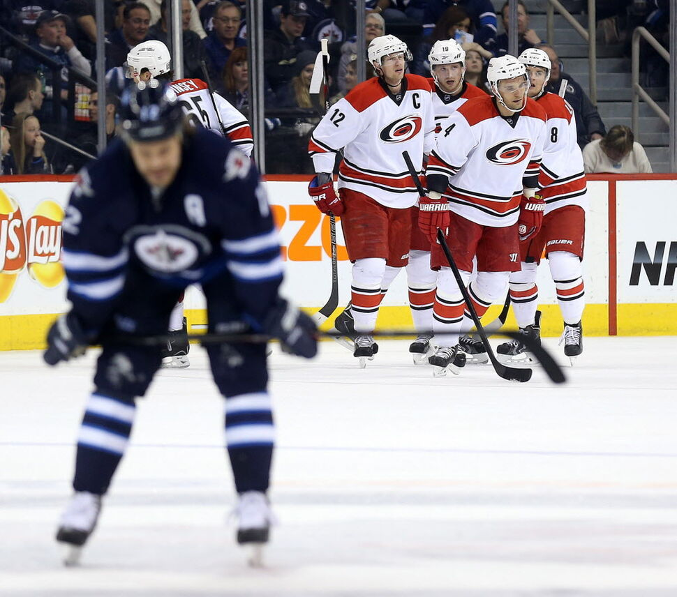 Winnipeg Jets' Olli Jokinen (12) looks on as Carolina Hurricanes' Eric Staal (12), Jiri Tlusty (19), Andrej Sekera (4) and Andrei Loktionov (8) celebrate Staal's goal during second the period. (TREVOR HAGAN / WINNIPEG FREE PRESS)