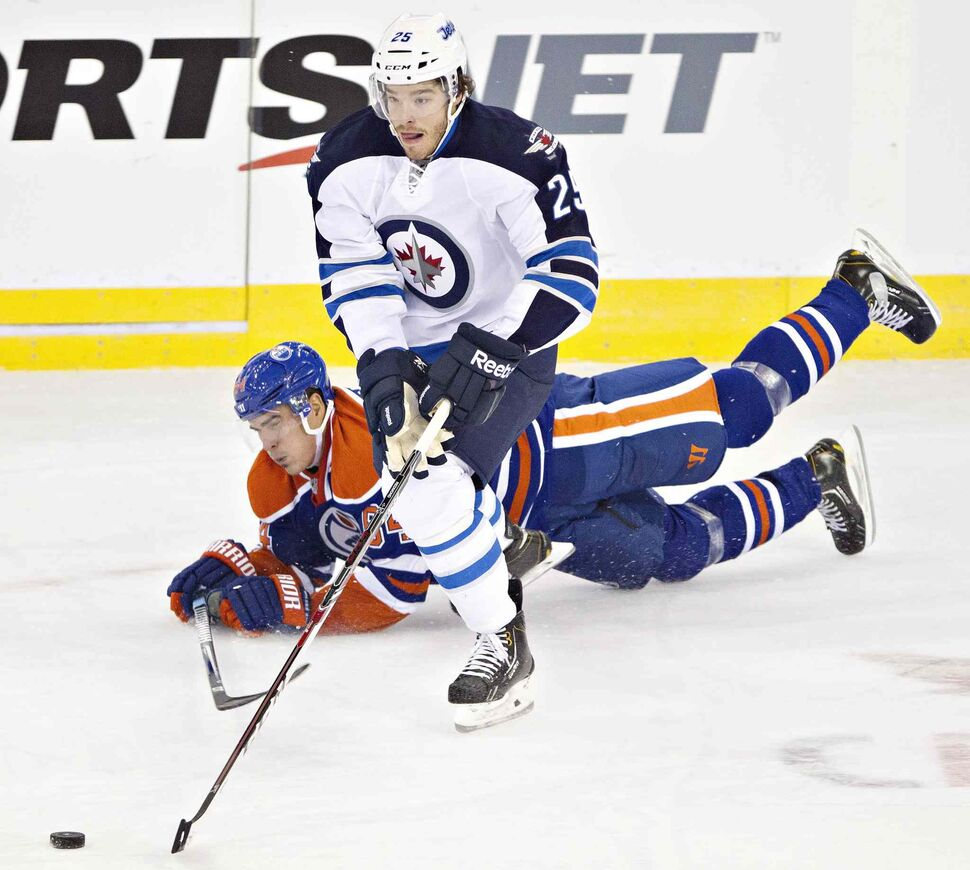 Zach Redmond (25) checks Nail Yakupov of the Edmonton Oilers during the second period. (Jason Franson / The Canadian Press)