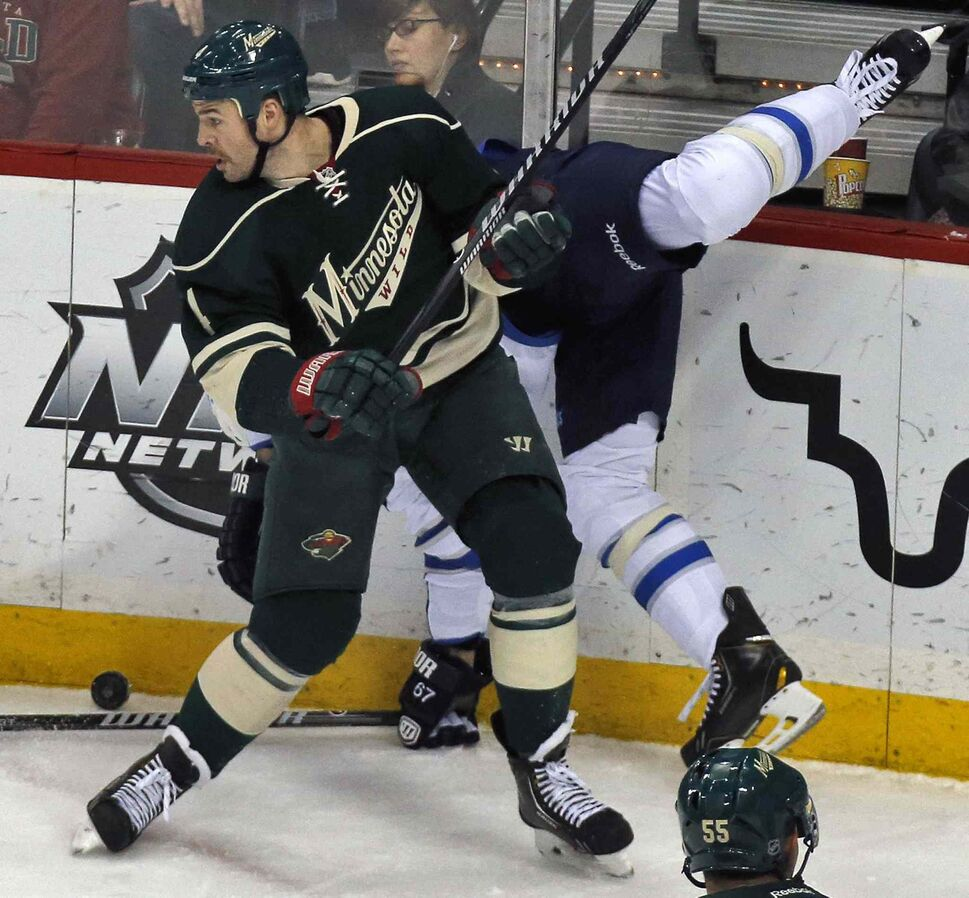 Clayton Stoner of the Minnesota Wild slams Michael Frolik of the Winnipeg Jets into the boards during the first period. (Marlin Levison / Minneapolis Star Tribune / MCT)