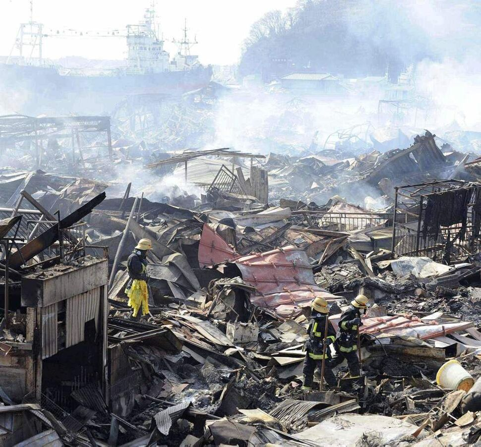 Rescuers conduct search operation amidst smoldering debris in Kesennuma, northern Japan Monday, March 14, 2011 following Friday's massive earthquake and the ensuing tsunami. (AP Photo/Yomiuri Shimbun, Miho Ikeya)