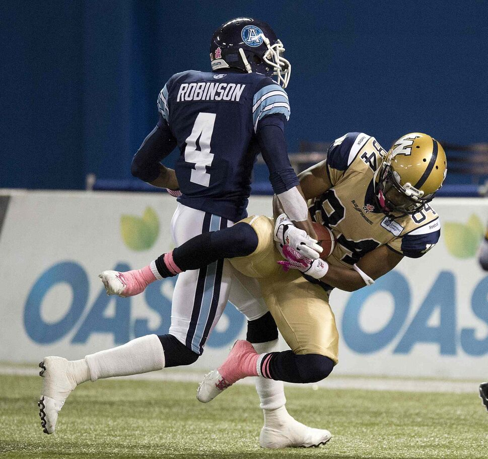 Toronto Argonauts defensive back Jamie Robinson tackles Winnipeg Blue Bombers slot back Wallace Miles as he hauls in a touchdown pass during the first half. (Frank Gunn / The Canadian Press)