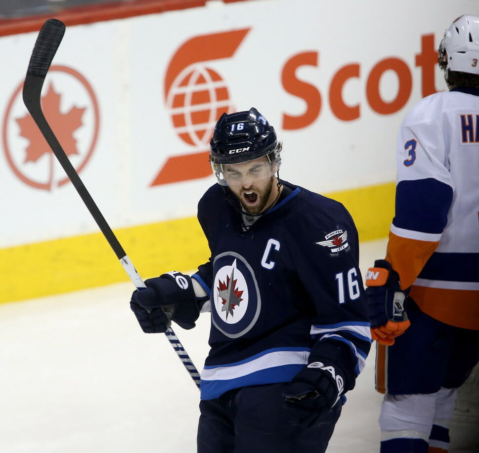 Winnipeg Jets' Andrew Ladd (16) celebrates opening the scoring against the New York Islanders' as Travis Hamonic (3) looks on during the first period.  (Trevor Hagan / THE CANADIAN PRESS)