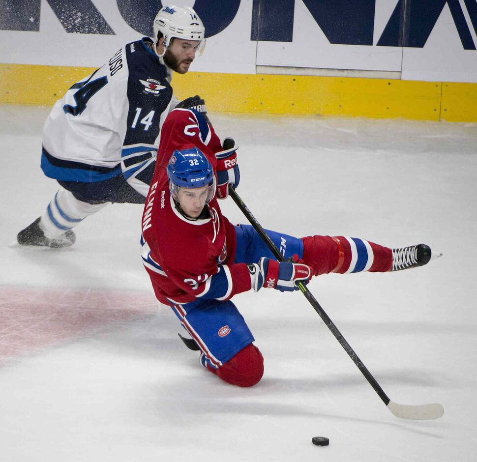 Montreal Canadiens' Brian Flynn, right, goes down as he tries to skate away from Winnipeg Jets' Anthony Peluso during third period NHL action Sunday. (Peter Mccabe / THE CANADIAN PRESS)