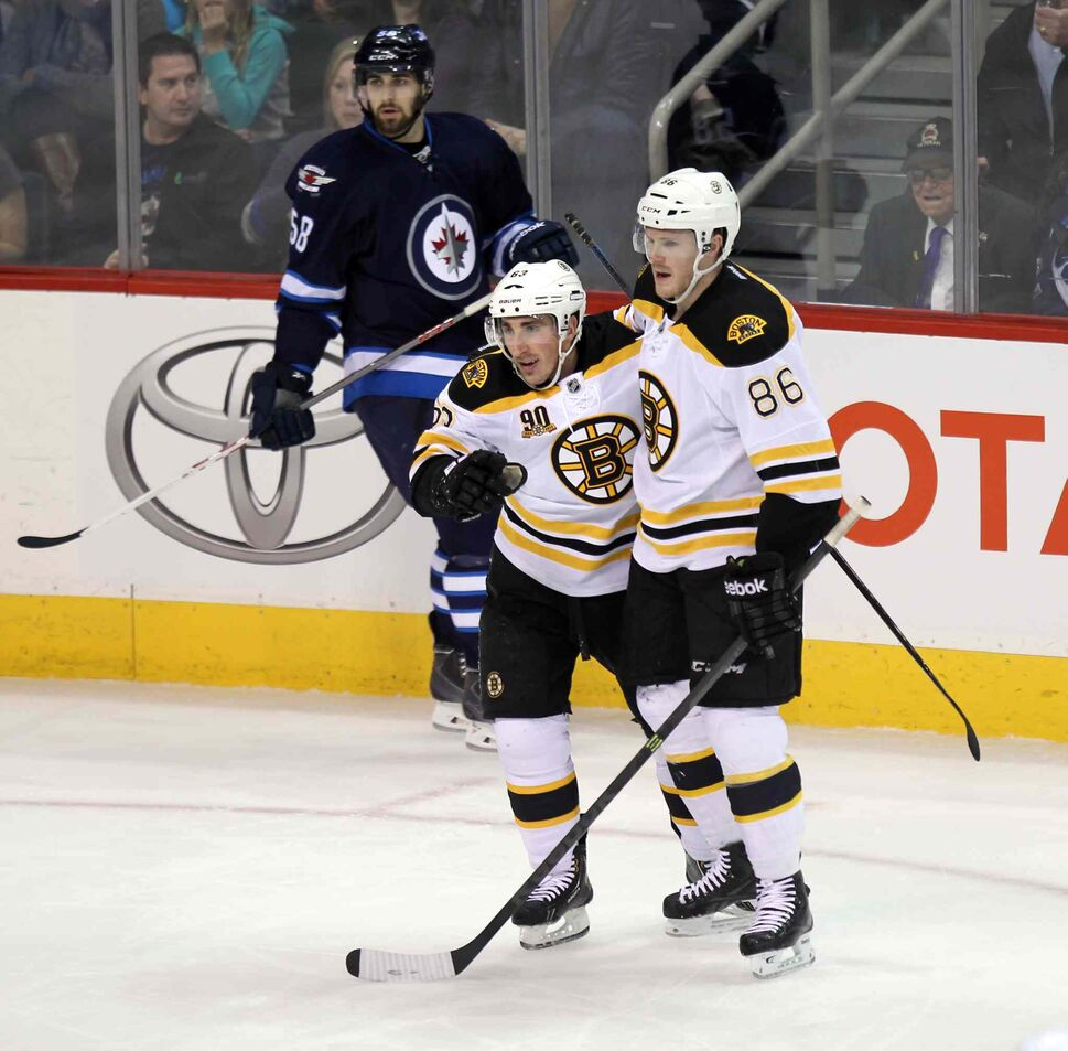 The Boston Bruins' Kevan Miller (#86) pats Brad Marchand on the back for scoring the first goal of Thursday's game at the MTS Centre. (Phil Hossack / Winnipeg Free Press)