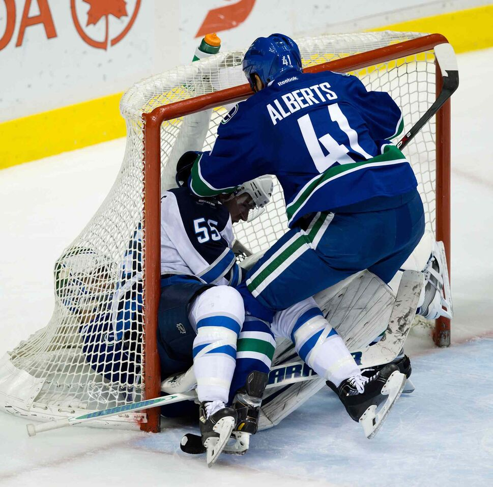 Winnipeg Jets forward Mark Scheifele (centre) falls on Vancouver Canucks goalie Eddie Lackas Andrew Alberts (right) tries to pull him out of the net during the second period. (DARRYL DYCK / THE CANADIAN PRESS)