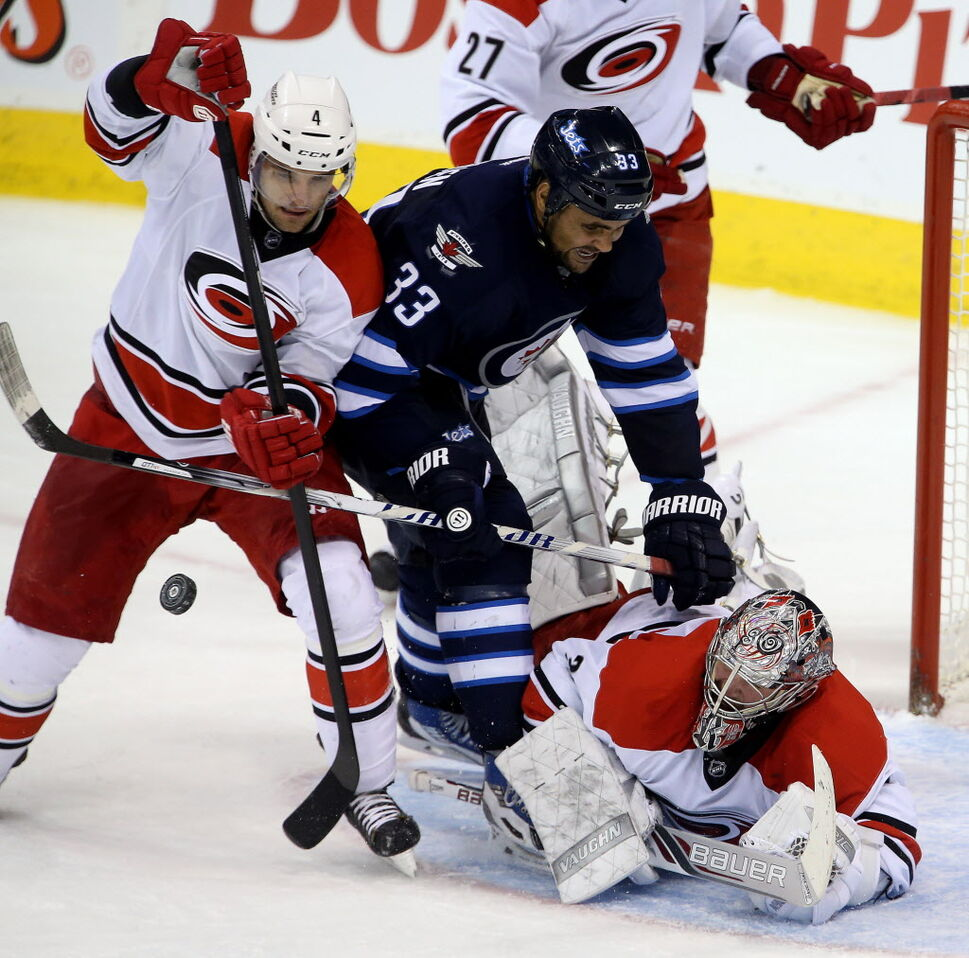 Carolina Hurricanes' Andrej Sekera (4) battles with Winnipeg Jets' Dustin Byfuglien (33) in front of goaltender Cam Ward (30) during third period NHL hockey action at MTS Centre in Winnipeg. (TREVOR HAGAN / WINNIPEG FREE PRESS)