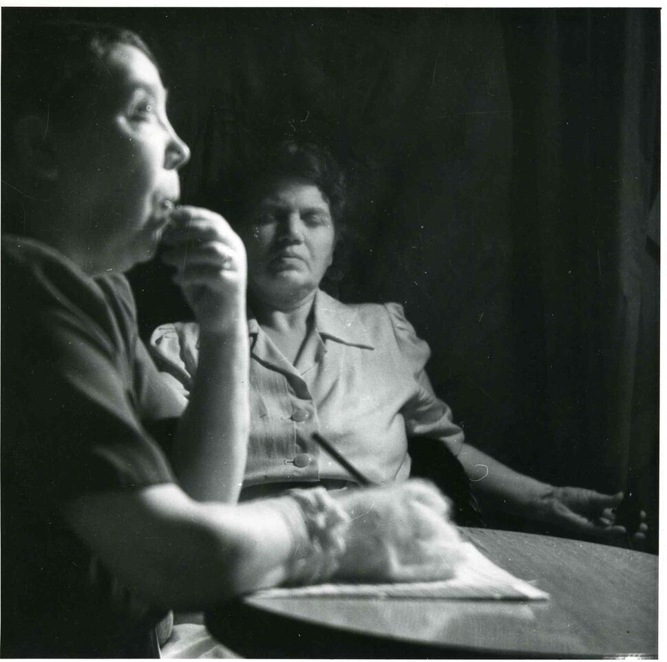A photograph of the medium, Mary Marshall, writing a letter in complete darkness while under the control of the spirit, Walter, during a seance at the home of Sylvia Barber ca. 1947-1951.  (UofM Archives/Hamilton Family fonds) ( UofM Archives/Hamilton Family fonds)