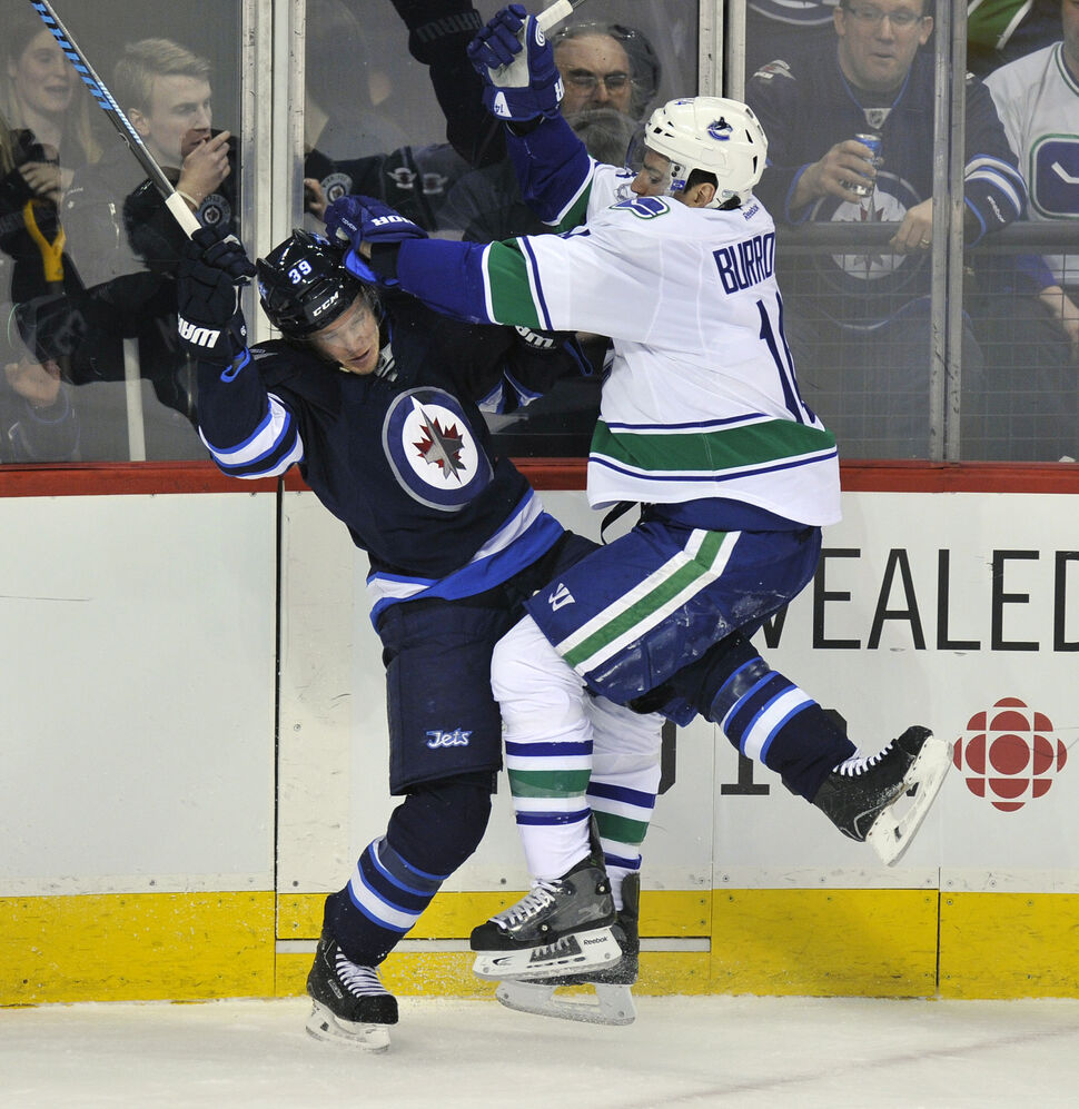 Winnipeg Jets' Tobias Endstrom runs Vancouver Canucks' Alexandre Burrows during the first period of Friday's game. (Fred Greenslade  / Special for the WINNIPEG FREE PRESS)
