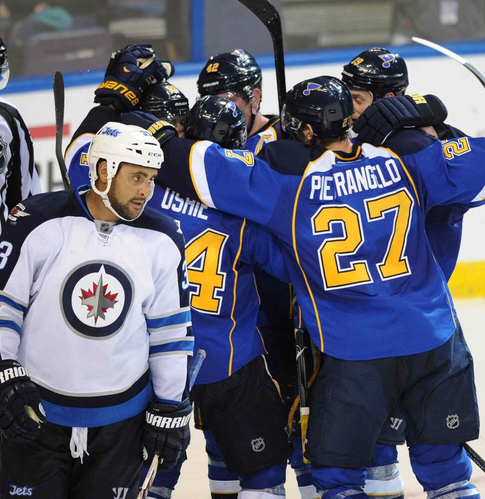 St. Louis Blues' Alex Pietrangelo, T.J. Oshie, David Backes and Jay Bouwmeester surround teammate Alexander Steen after his game-winning goal as Winnipeg Jets defenceman Dustin Byfuglien skates away dejectedly.