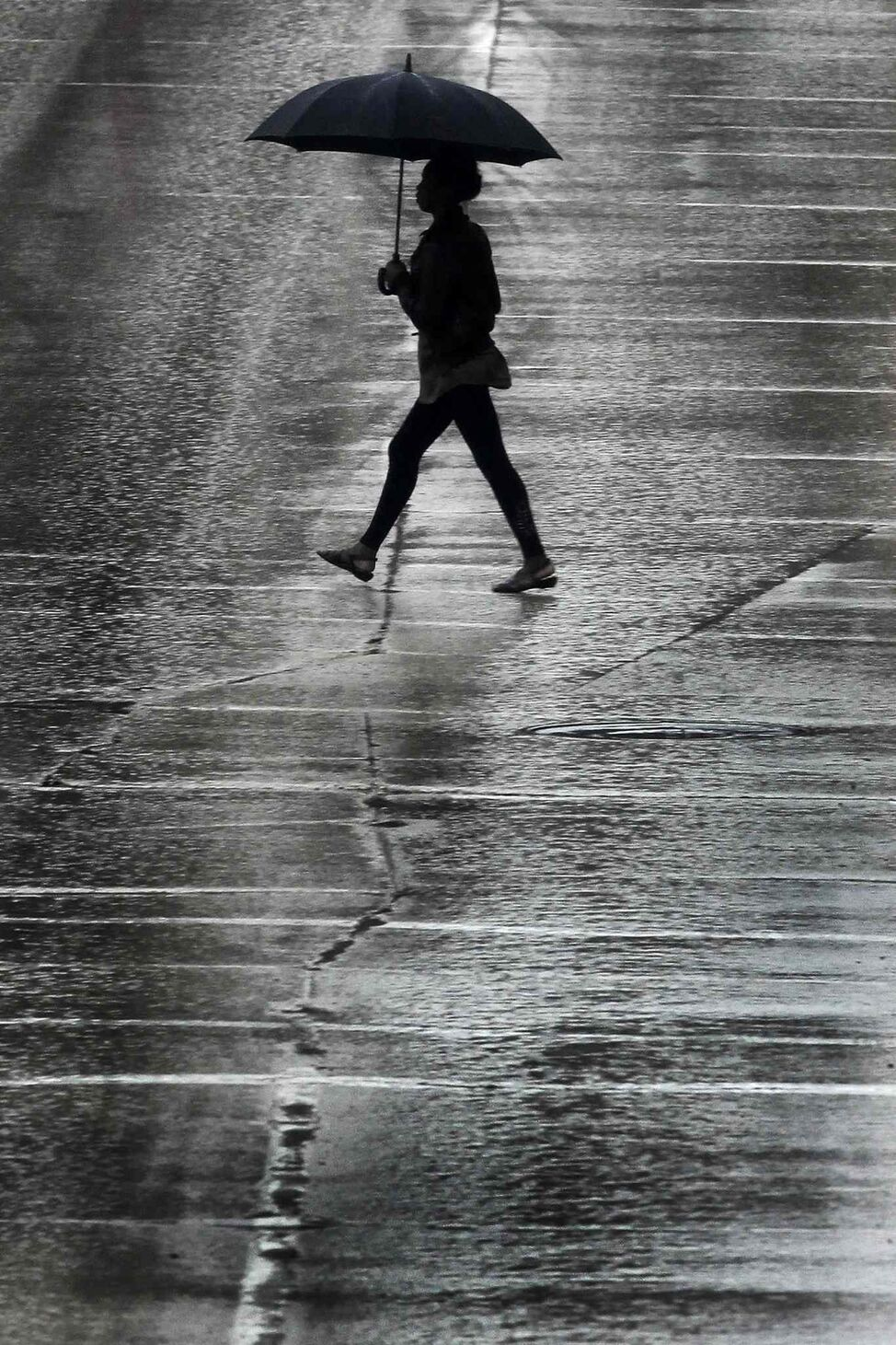 A pedestrian crosses Portage Avenue during a day of rainfall May 19, 2013.