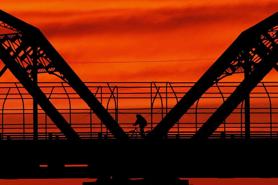 A cyclist crosses the Arlington Street Bridge Monday, June 3, 2013.