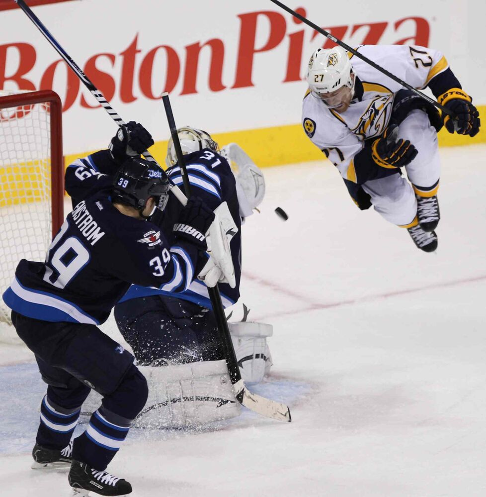Jets goalie Ondrej Pavelec is knocked back by Patric Hornqvist of the Nashville Predators in the third period. (Melissa Tait / Winnipeg Free Press)