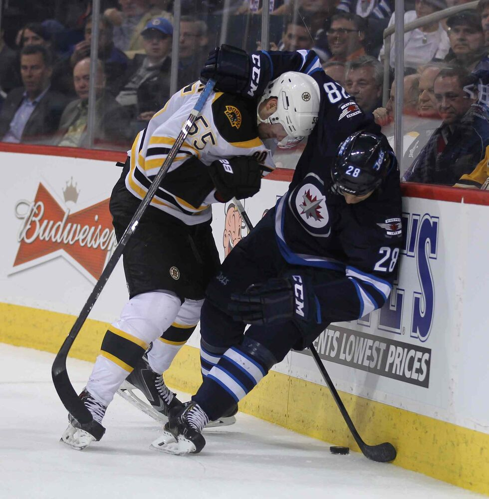 Bruins' Johnny Boychuk and Jets' Patrice Cormier battle it out behind the Bruins' net during the second period Thursday. (Phil Hossack / Winnipeg Free Press)