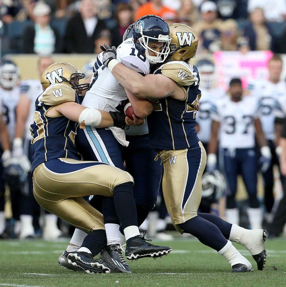 Argos quarterback Mitchell Gale gets sacked by Bombers defenders Greg Peach, right, and Zach Anderson during the first half. (TREVOR HAGAN / THE CANADIAN PRESS)
