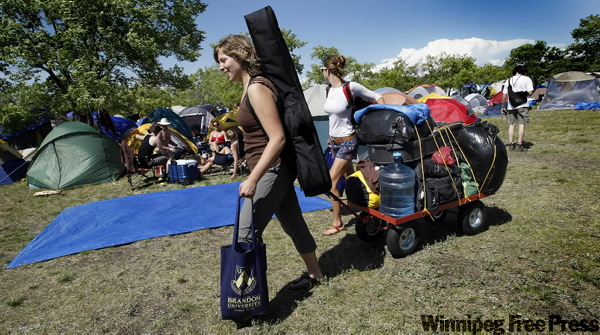 Deandra Tousignant (left) and Karli Brackenrebbe trail a carvan of camping gear behind them as they search the Folk Festival camp ground for a suitable tent site. (PHIL.HOSSACK@FREEPRESS.MB.CA)