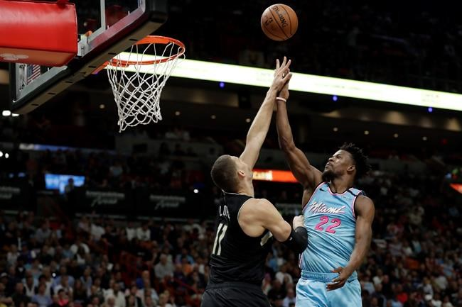 Miami Heat forward Jimmy Butler (22) goes up to shoot against Milwaukee Bucks center Brook Lopez (11) during the first half of an NBA basketball game, Monday, March 2, 2020, in Miami. (AP Photo/Wilfredo Lee)