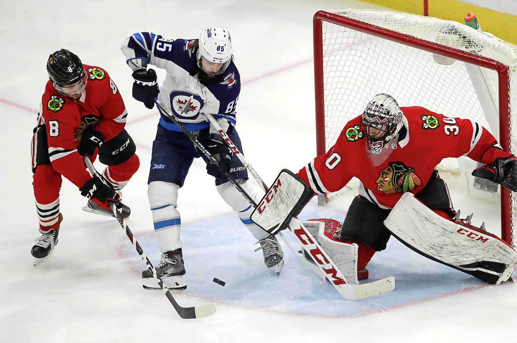 Chicago Blackhawks center Nick Schmaltz and goaltender Jeff Glass defend against Winnipeg Jets center Mathieu Perreault during the third period Friday in Chicago.