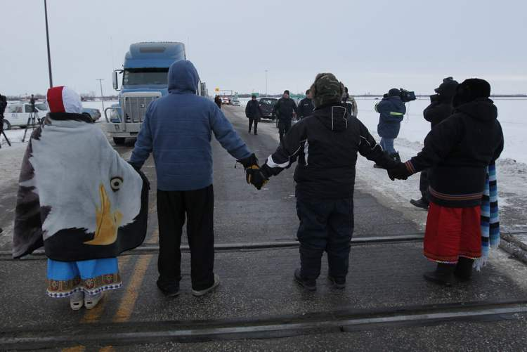 RCMP officers approach four aboriginal protestors at a blockade of a CN railroad track just west of Portage La Prairie, Man.