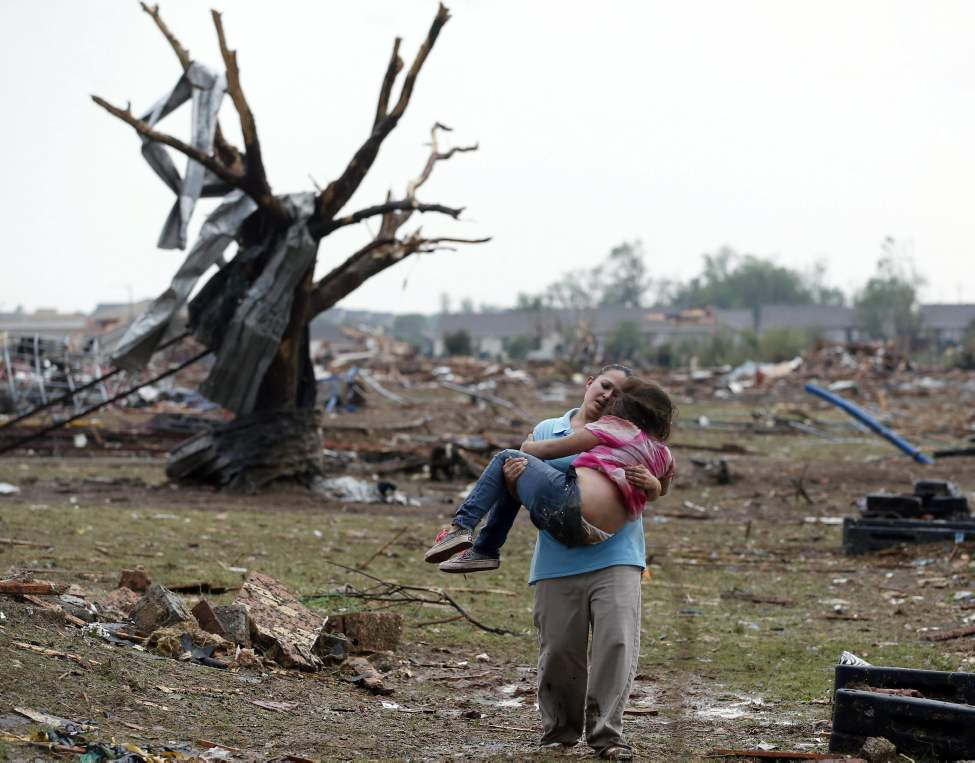A woman carries a child through a field near the collapsed Plaza Towers Elementary School in Moore, Okla., Monday. The relationship between the woman and the child was not immediately known. A tornado as much as a 1.6 kilometers wide with winds up to 320 km/h roared through the Oklahoma City suburbs Monday, flattening entire neighborhoods, setting buildings on fire and landing a direct blow on an elementary school.  (Sue Ogrocki / The Associated Press)