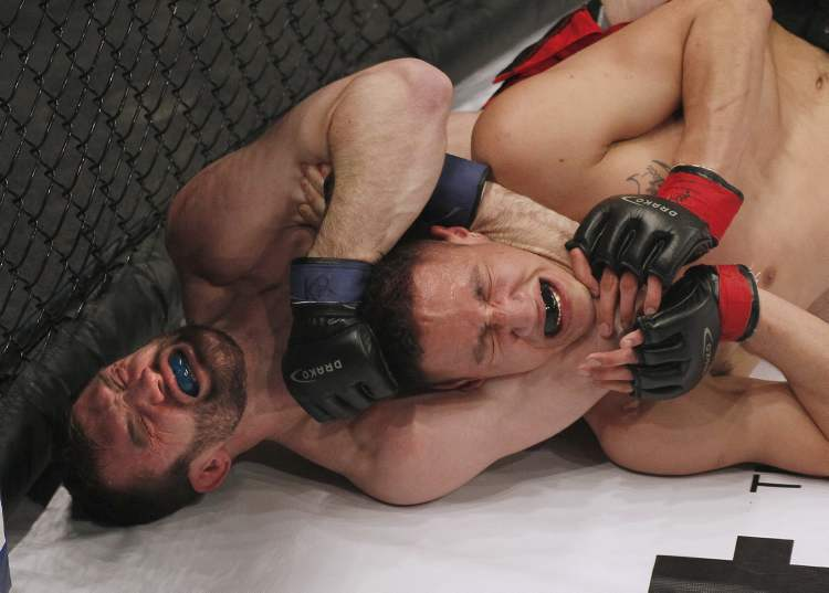Mitch Fryia chokes Dwight Sutherland in the Aggression Fighting Championships mixed martial arts competition at the Winnipeg Convention Centre.  John Woods / Winnipeg Free Press