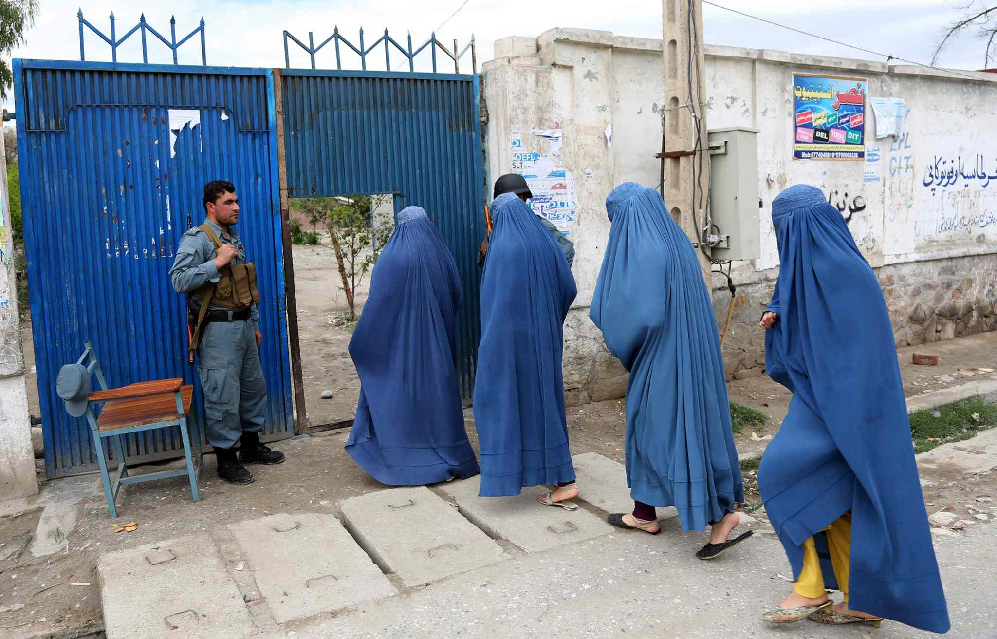 Afghan women enter a poling station to vote in Jalalabad, east of Kabul, Afghanistan, Saturday, April 5. Afghan voters lined up for blocks at polling stations nationwide on Saturday, defying a threat of violence by the Taliban.