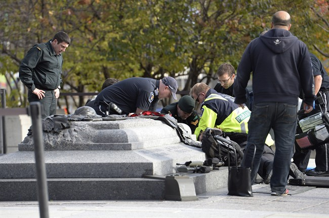 A soldier, police and paramedics tend to a soldier shot at the National Memorial near Parliament Hill in Ottawa on Wednesday Oct.22, 2014. THE CANADIAN PRESS/Adrian Wyld