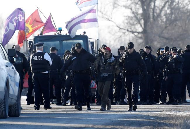 Ontario Provincial Police officers lead away a man after making an arrest at a rail blockade in Tyendinaga Mohawk Territory, near Belleville, Ont., on Monday Feb. 24, 2020, as they protest in solidarity with Wet'suwet'en Nation hereditary chiefs attempting to halt construction of a natural gas pipeline on their traditional territories. THE CANADIAN PRESS/Adrian Wyld