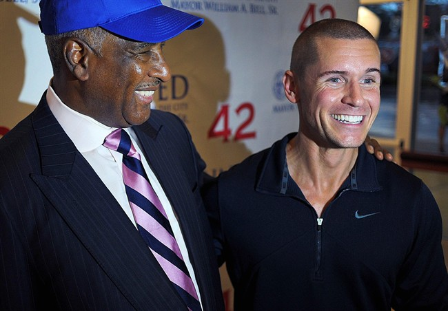 """Alabama native and actor Linc Hand, right, poses for pictures with Birmingham, Ala., Mayor William Bell at a screening of the Jackie Robinson movie """"42"""" in Birmingham, Ala. Hand plays Pittsburgh Pirates pitcher Fritz Ostermueller in the film. Some of the scenes in the movie were filmed in Birmingham. (AP Photo/AL.com, Tamika Moore)."""