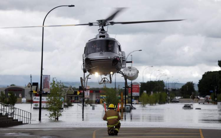 A helicopter carrying evacuated residents lands on a road in High River, Alta.  (Jeff McIntosh / The Canadian Press)