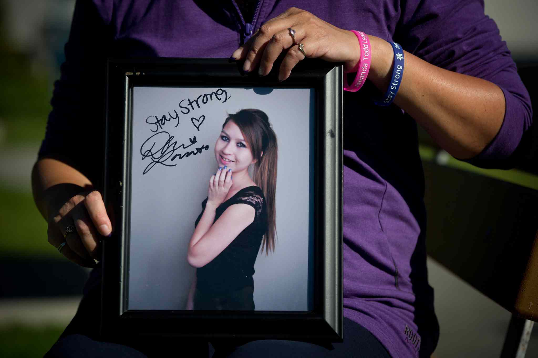 Carol Todd holds a photo of her late daughter, Amanda Todd, signed by singer Demi Lovato with the words 'Stay Strong.'