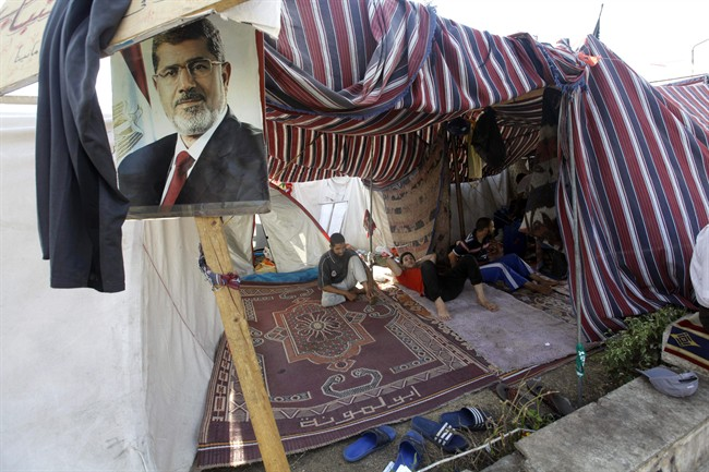 """Supporters of Egypt's ousted President Mohammed Morsi, seen in the poster, rest in a tent in a park in front of Cairo University, where protesters have installed their camp in Giza, southwest of Cairo, Egypt, Thursday, Aug. 1, 2013. Authorities offered """"safe passage and protection"""" Thursday for thousands of supporters of ousted President Mohammed Morsi if they end their two large sit-ins in Cairo. The Interior Ministry's offer appears to be the first step by Egypt's new leadership to clear away the Morsi supporters from where they have been camped since shortly before he was toppled by the army July 3. (AP Photo/Amr Nabil)"""