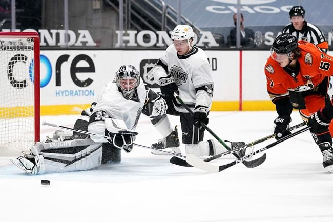 Los Angeles Kings goaltender Jonathan Quick, left, deflects a shot by Anaheim Ducks center Rickard Rakell, right, as defenseman Tobias Bjornfot defends during the second period of an NHL hockey game Friday, April 30, 2021, in Anaheim, Calif. (AP Photo/Mark J. Terrill)
