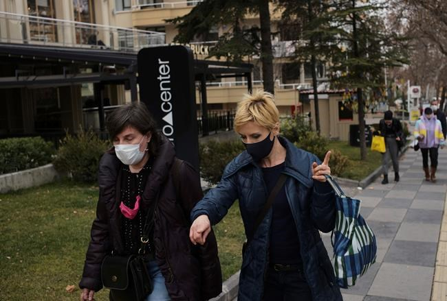 People wearing masks to help protect against the spread of coronavirus, walk along a busy shopping street, in Ankara, Turkey, Tuesday, Jan. 12, 2021. Turkish President Recep Tayyip Erdogan said Monday Turkey hopes to begin vaccinations against the coronavirus later this week, after the Turkish authorities complete their final tests for the regulatory approval China's SinoVac vaccine. (AP Photo/Burhan Ozbilici)