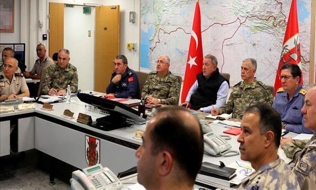 Turkey's Defense Minister Hulusi Akar, center, sits with Turkish army's top commanders in an operation room at the army headquarters, in Ankara, Turkey, Wednesday, Oct. 9, 2019. Turkey's Defense Ministry says Turkish ground forces have moved across the border to fight against Kurdish fighters in northeastern Syria, hours after Turkish jet and artillery pounded areas in Syria's northern border. (Turkish Defence Ministry via AP, Pool)