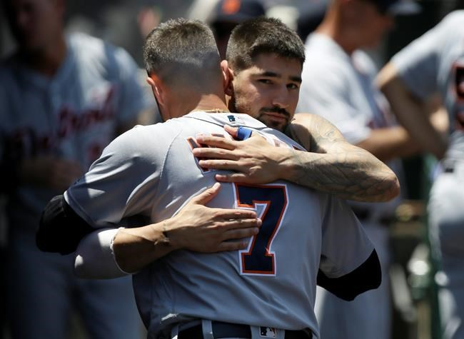 Detroit Tigers' Nicholas Castellanos, right, hugs farewell to Jordy Mercer in the dugout, after Castellanos is traded to the Chicago Cubs, during the first inning of a baseball game against the Los Angeles Angels in Anaheim, Calif., Wednesday, July 31, 2019. (AP Photo/Alex Gallardo)