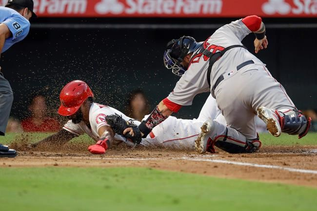Los Angeles Angels' Luis Rengifo, left, scores past Boston Boston Red Sox catcher Sandy Leon on a single by Mike Trout during the second inning of a baseball game in Anaheim, Calif., Saturday, Aug. 31, 2019. (AP Photo/Chris Carlson)