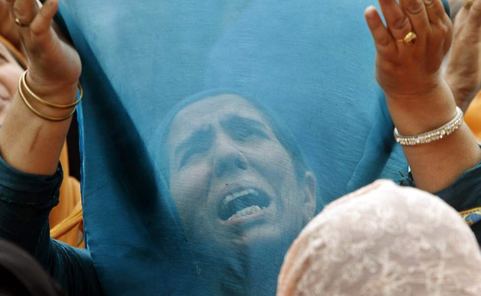 A Kashmiri Muslim woman prays as a head priest, unseen, displays a relic, believed to be a hair from the beard of the Prophet Mohammad at the Hazratbal Shrine on the outskirts of Srinagar, India. Devotees thronged the Hazratbal shrine during Muslim festival of Mehraj-u-Alam, believed to mark the ascension of Prophet Mohammed to Heaven. (AP Photo/Mukhtar Khan)