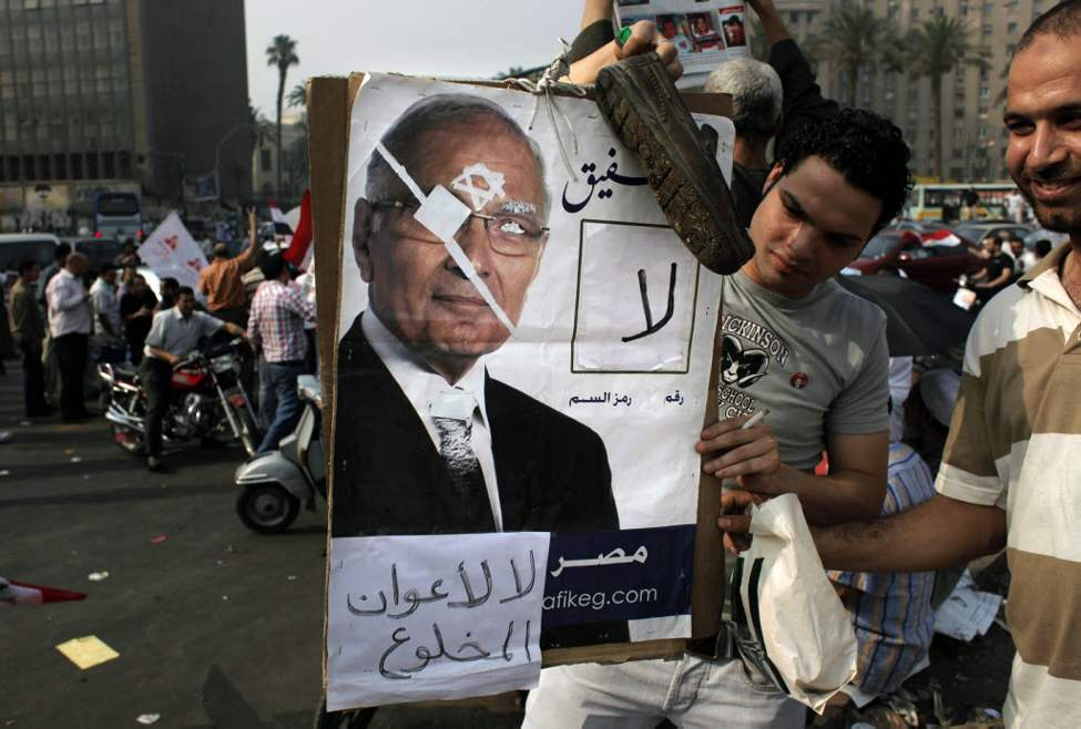 "Supporters of presidential candidate Mohammed Morsi carry a poster with a defaced picture of his rival, Ahmed Shafiq, with Arabic that reads ""No No for the aid of the ousted,"" during celebrations  claiming victory for Morsi in Tahrir Square, Cairo, Egypt. The Muslim Brotherhood declared early Monday that its candidate, Mohammed Morsi, won Egypt's presidential election, which would be the first victory of an Islamist as head of state in the stunning wave of protests demanding democracy that swept the Middle East the past year. (AP Photo/Nasser Nasser)"