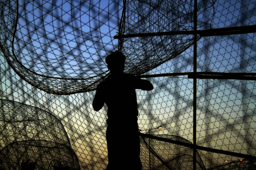 A fisherman works on fish traps at sunset in Malkiya village, Bahrain, on the Persian Gulf coast. (AP Photo/Hasan Jamali)