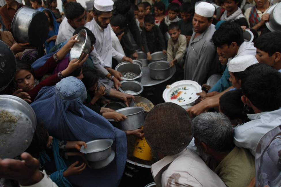 Afghans get free food donated by a private charity as they break their fast during a holy month of Ramadan in Jalalabad, east of Kabul. (AP Photo/ Rahmat Gul)