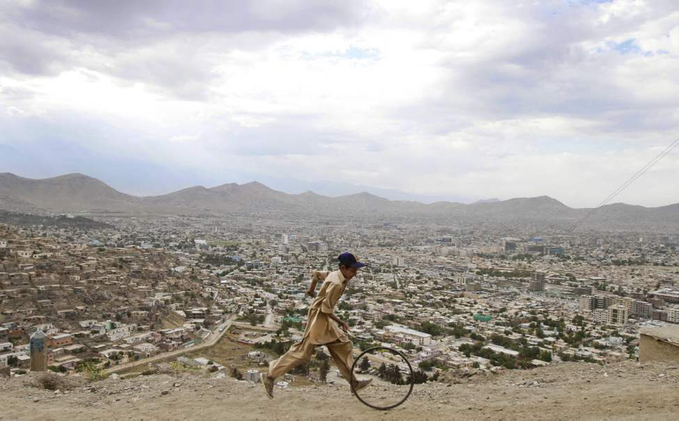 An Afghan boy pushes a wheel on a hill in Kabul. (AP Photo/Ahmad Jamshid)