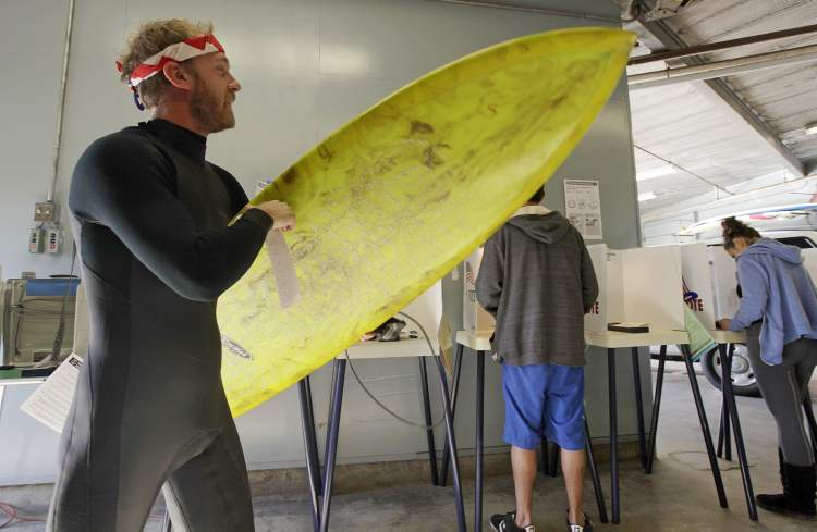 """After voting, Mike Weigart, 30, carries his ballot and his surfboard to the ballot box at the polling place at the Venice Beach lifeguard headquarters in Los Angeles Tuesday, Nov. 6, 2012. Weigart said, """"It's awesome the polling place is where I surf.""""  (Reed Saxon / The Associated Press)"""