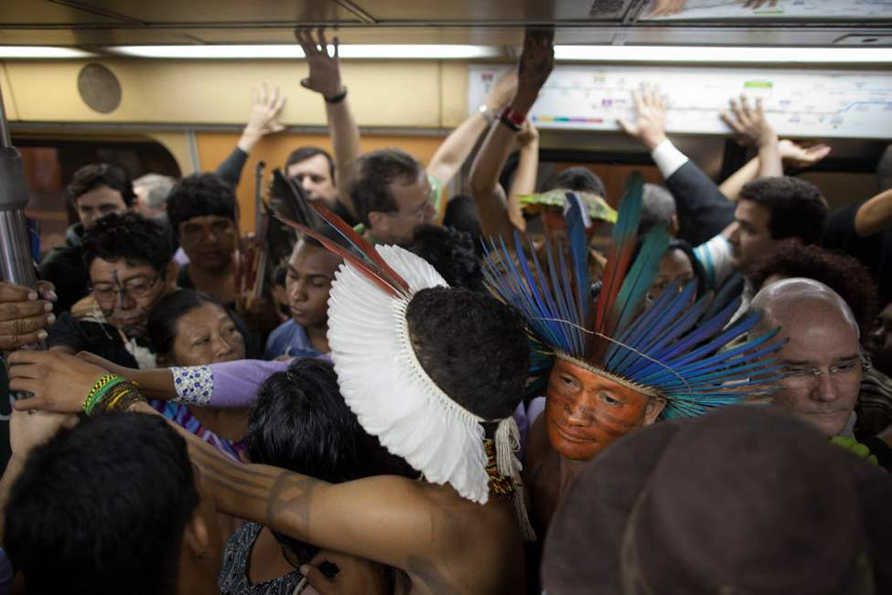 Indigenous squeeze into a subway train as they ride to the People's Summit for Social and Environmental Justice in defence of the commons, a parallel event taking place alongside the United Nations Conference on Sustainable Development, or Rio+20, in Rio de Janeiro, Brazil. The Earth summit runs through June 22, with three final days of high-profile talks among some 130 top leaders from nations around the globe. (AP Photo/Felipe Dana)