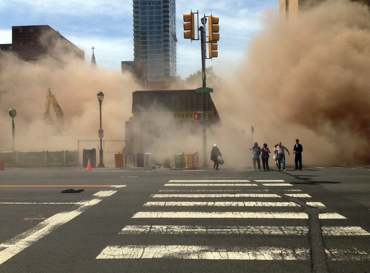 A dust cloud rises as people run from the scene of the building collapse.