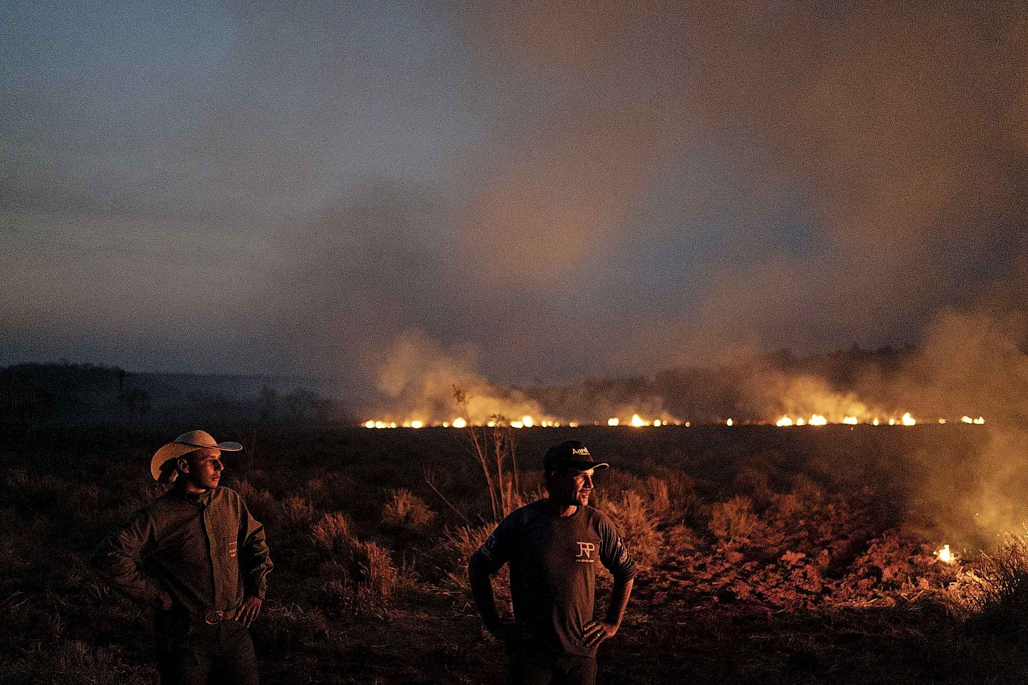 Neri dos Santos Silva, center, watches an encroaching fire threat on Friday after digging trenches to keep the flames from spreading to the farm he works on.