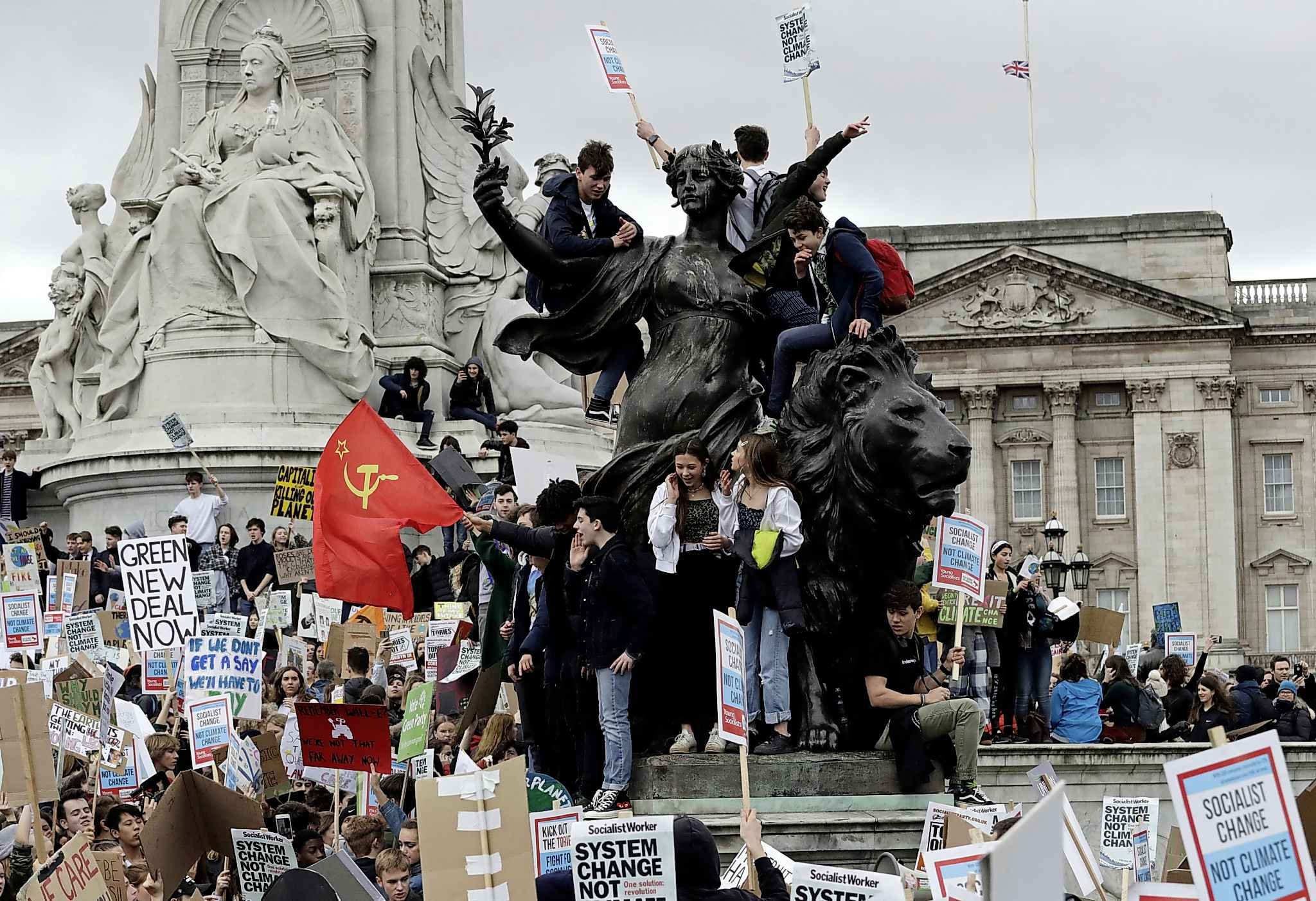 Youngsters stand on the Queen Victoria Memorial outside Buckingham Palace as they take part in a worldwide student climate protest in London, England on March 15 (Matt Dunham / The Associated Press files)